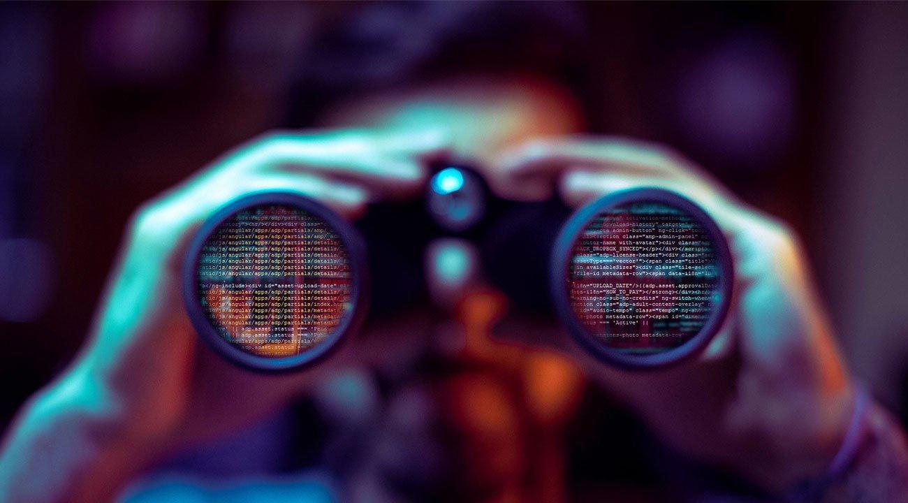 Man with binoculars looking at code