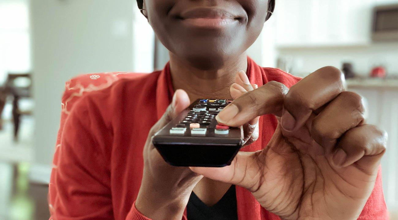 Woman holding TV remote pressing power button
